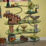 Patina bronze shelves. Carved and painted glass by Alisha Volotzky.